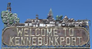 "Metal ""Welcome to Kennebunkport"" sign with blue sky background."