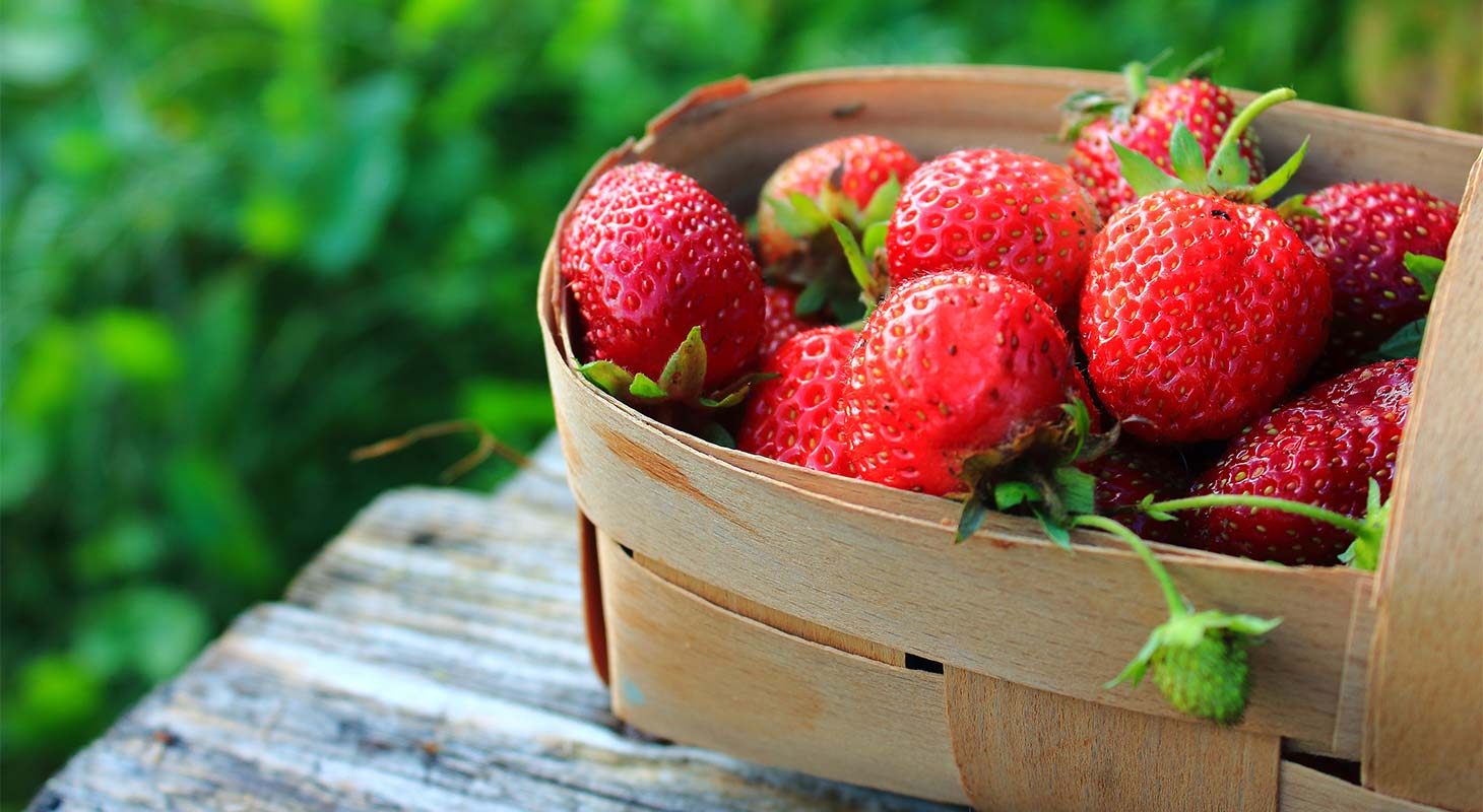 A basket of red strawberries on a wooden table