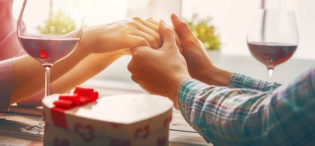 A couple holding hands with a heart shaped box on the table