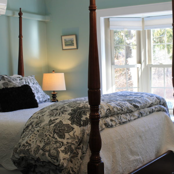 Four poster queen bed in a room with bay windows