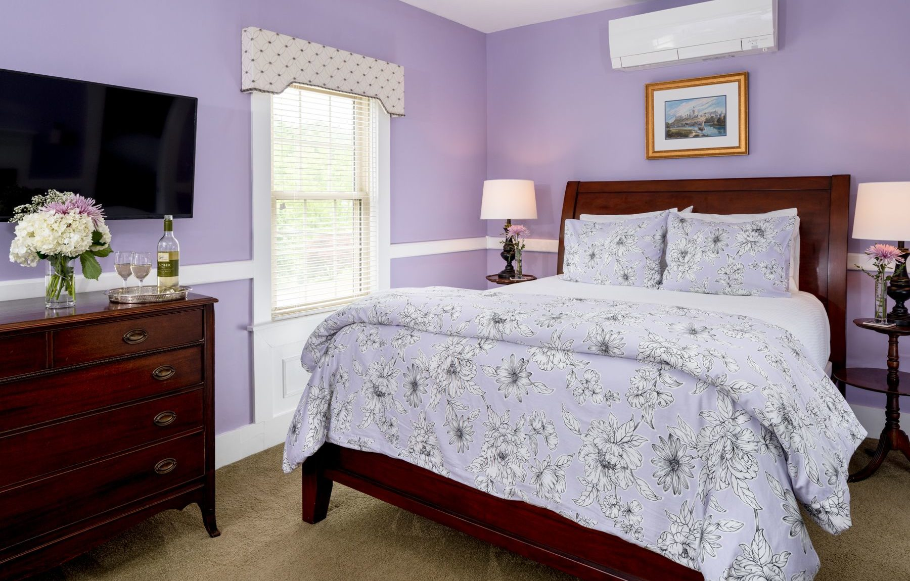 Queen bed in a spacious room with lilac walls