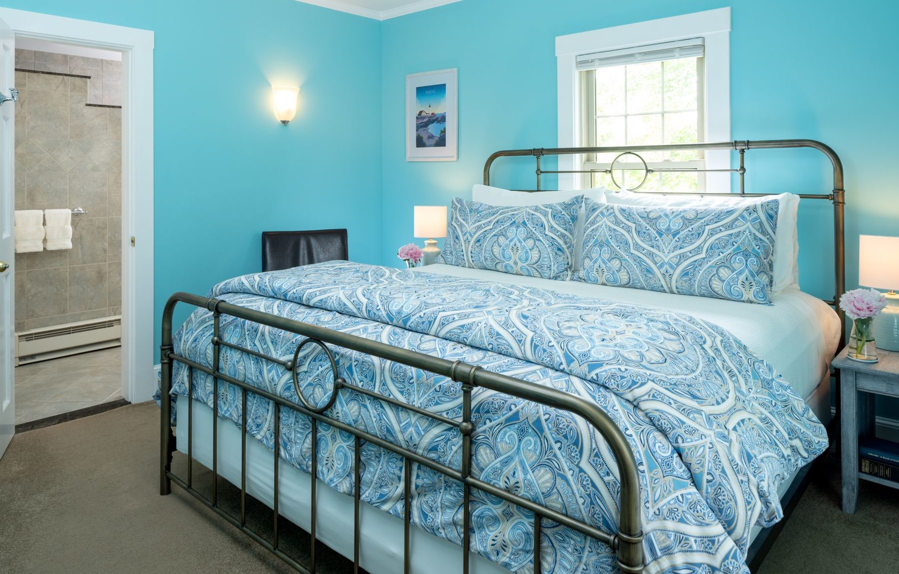 Metal bed with blue paisley duvet and bedside table with lamp