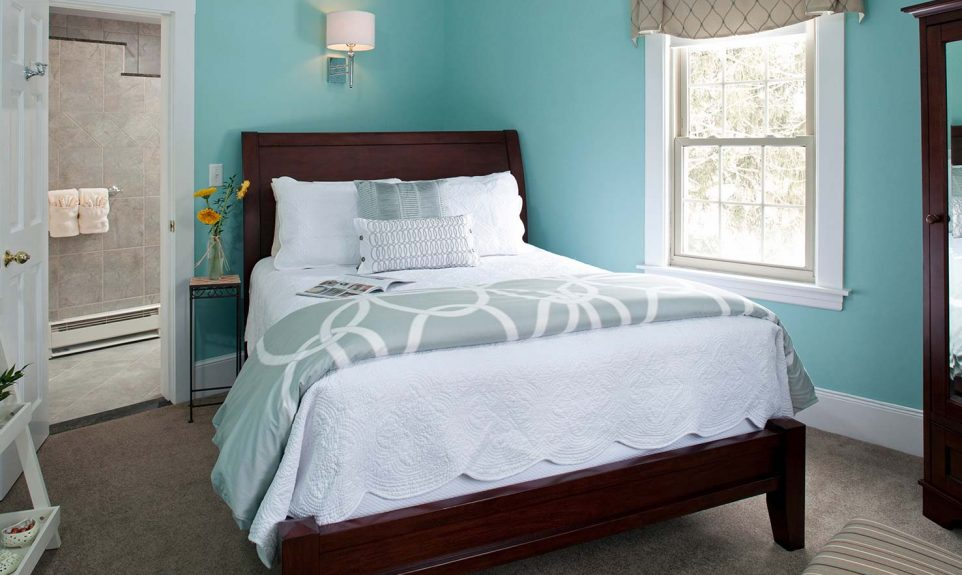 Queen bed in a room with light blue walls and a window overlooking a garden