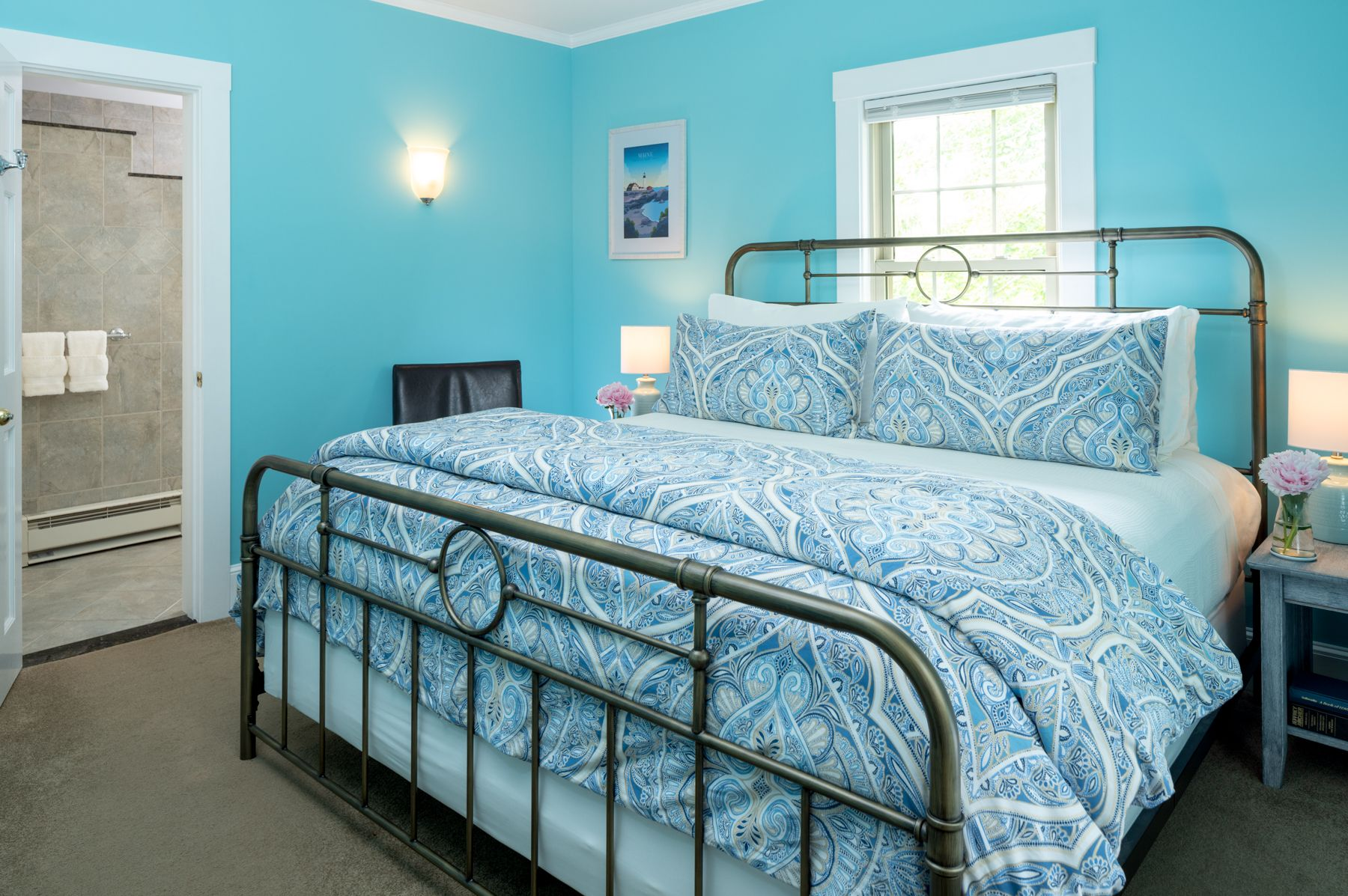 King bed in a room with light blue walls and a window overlooking a garden