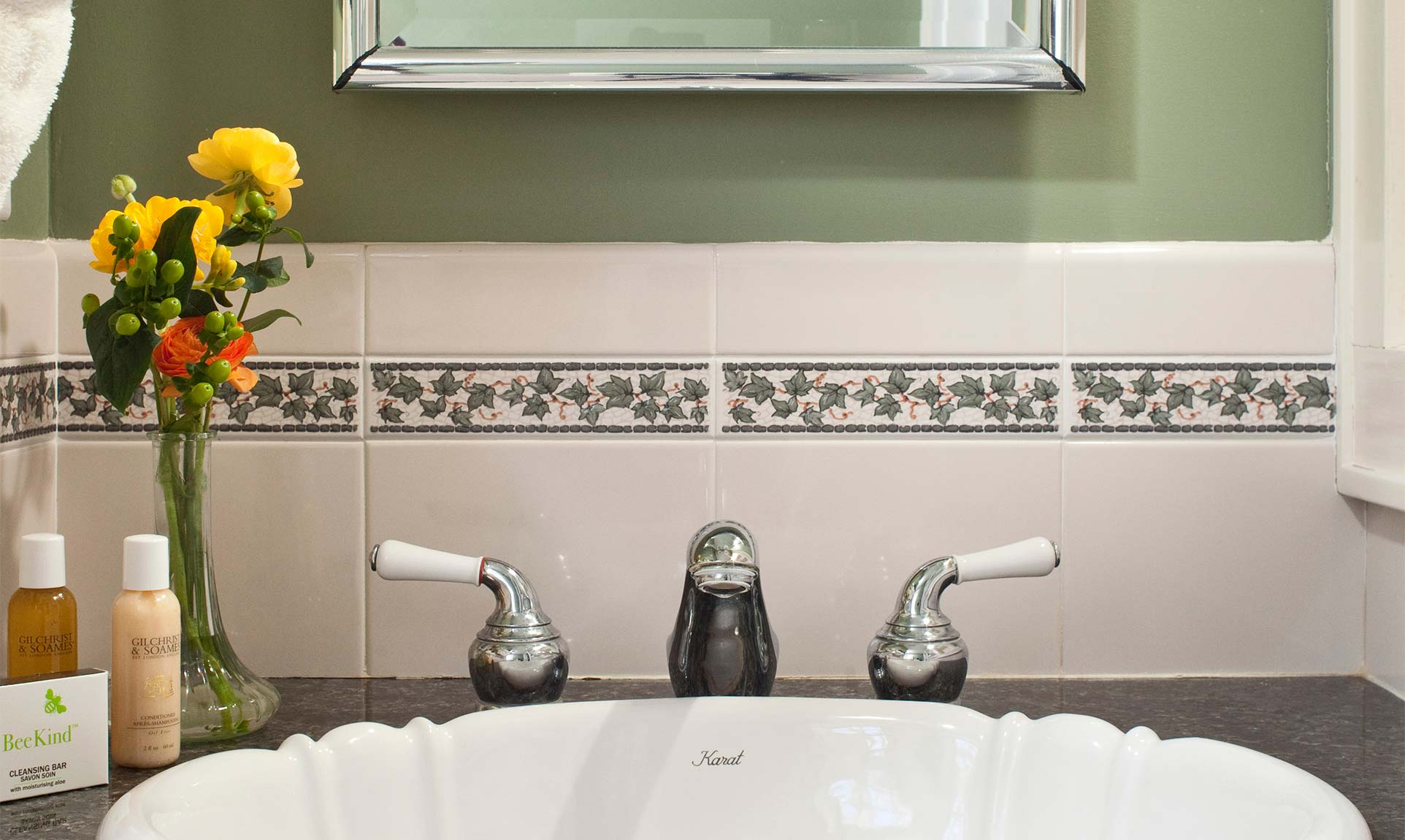 Bathroom sink with flowers in a vase and toiletries