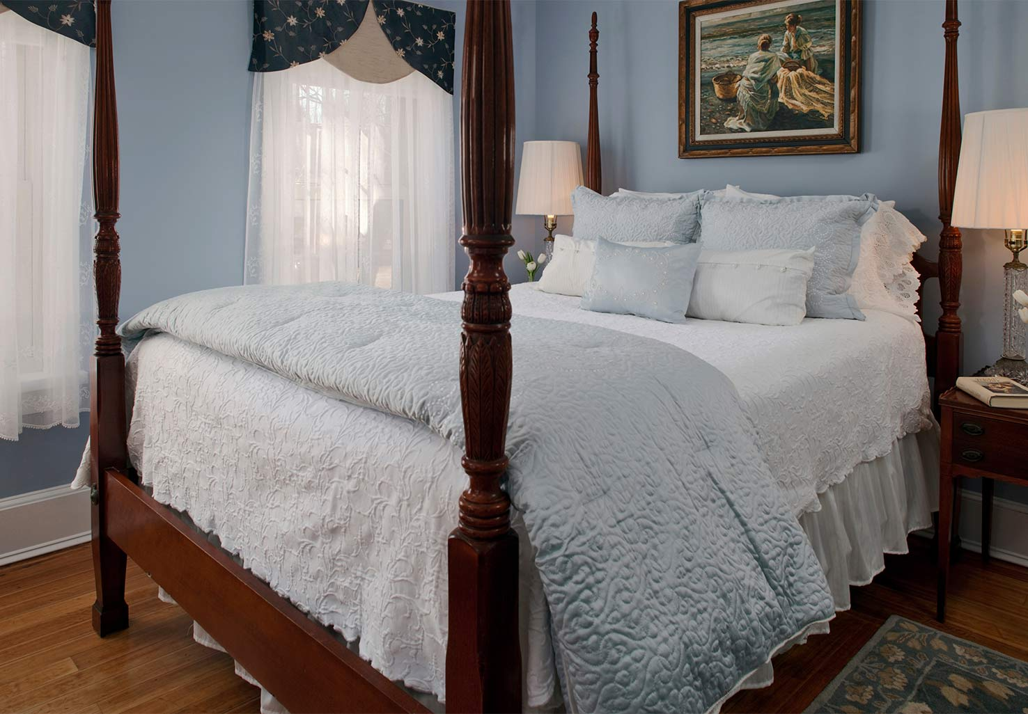Four poster queen bed in a room with light blue walls
