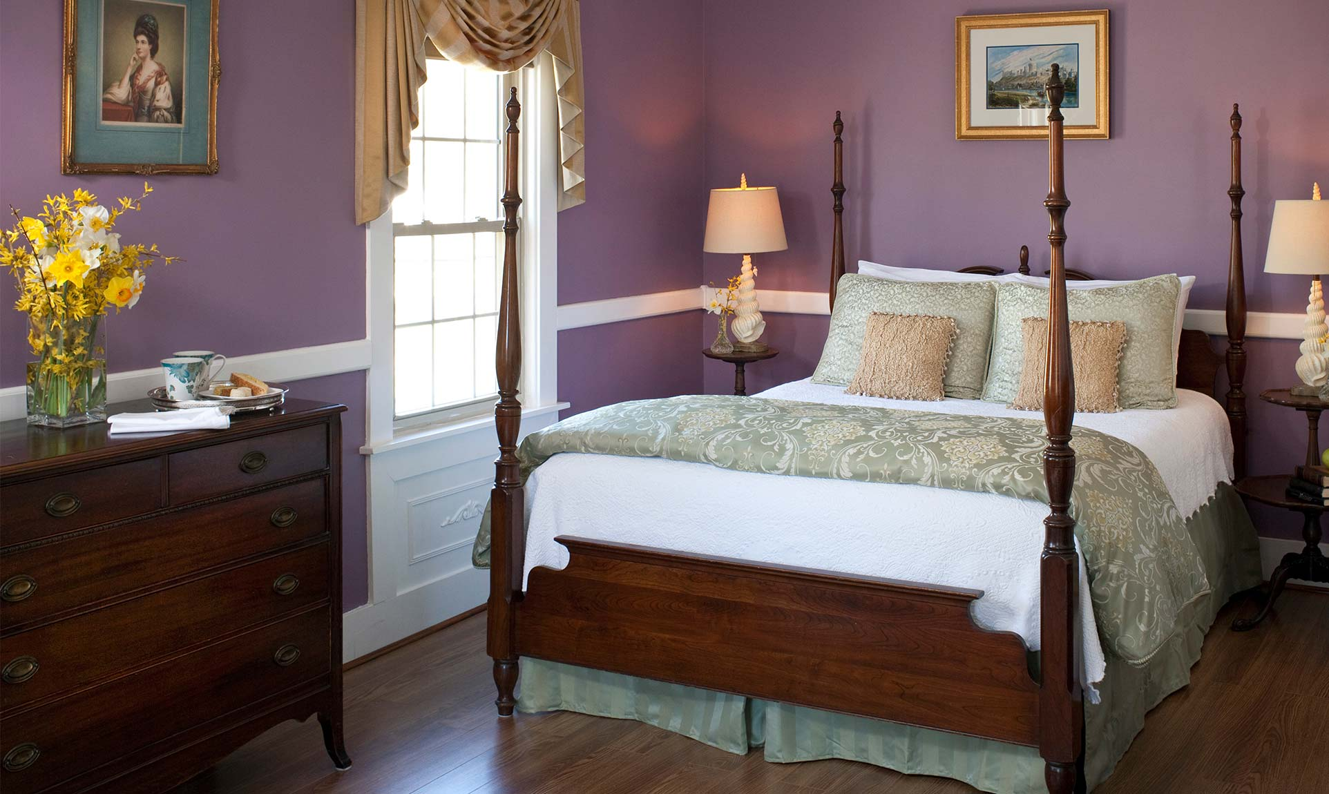Four poster queen bed in a spacious room with lavender walls