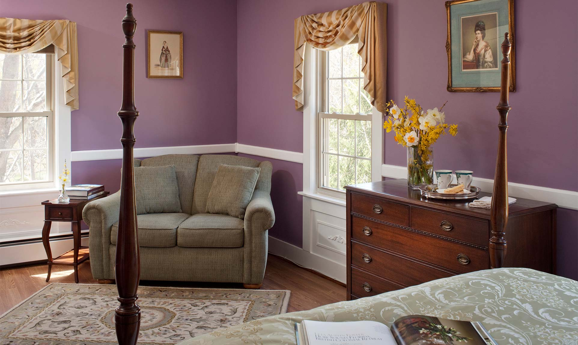 Spacious seating area with a 5 drawer dresser and two windows