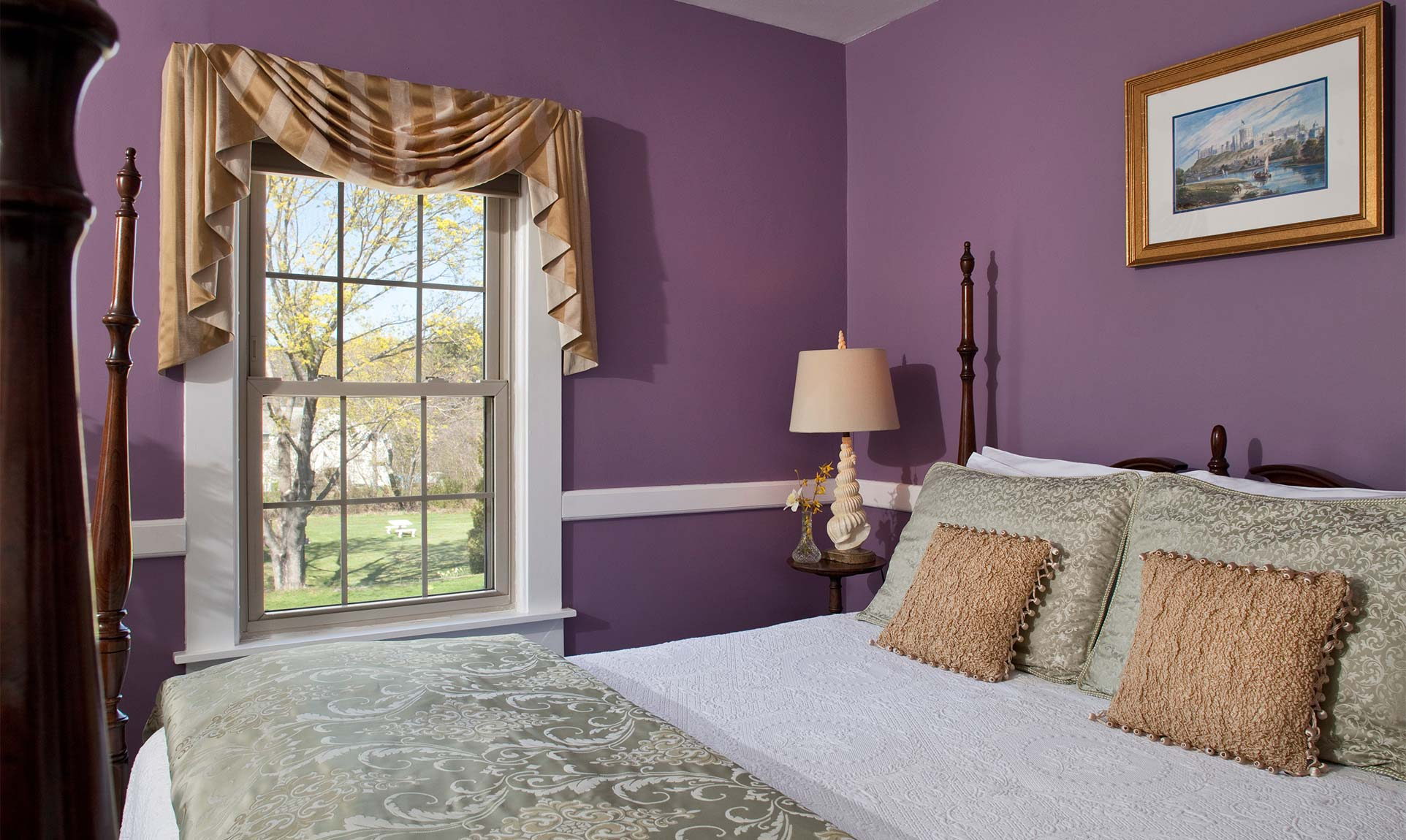 Queen bed and a window overlooking a yard