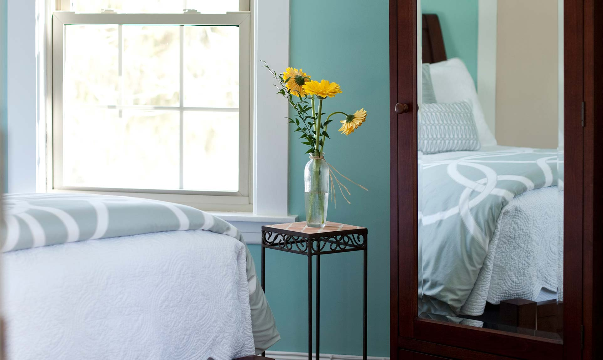 Full length mirror next to a side table with sunflowers in a vase