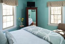 Queen bed in a room with two windows and a seating area