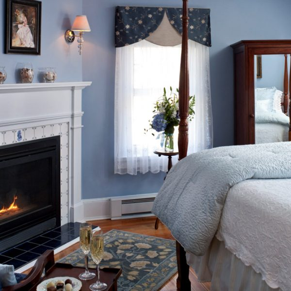 Fireplace and queen bed in a Camden room