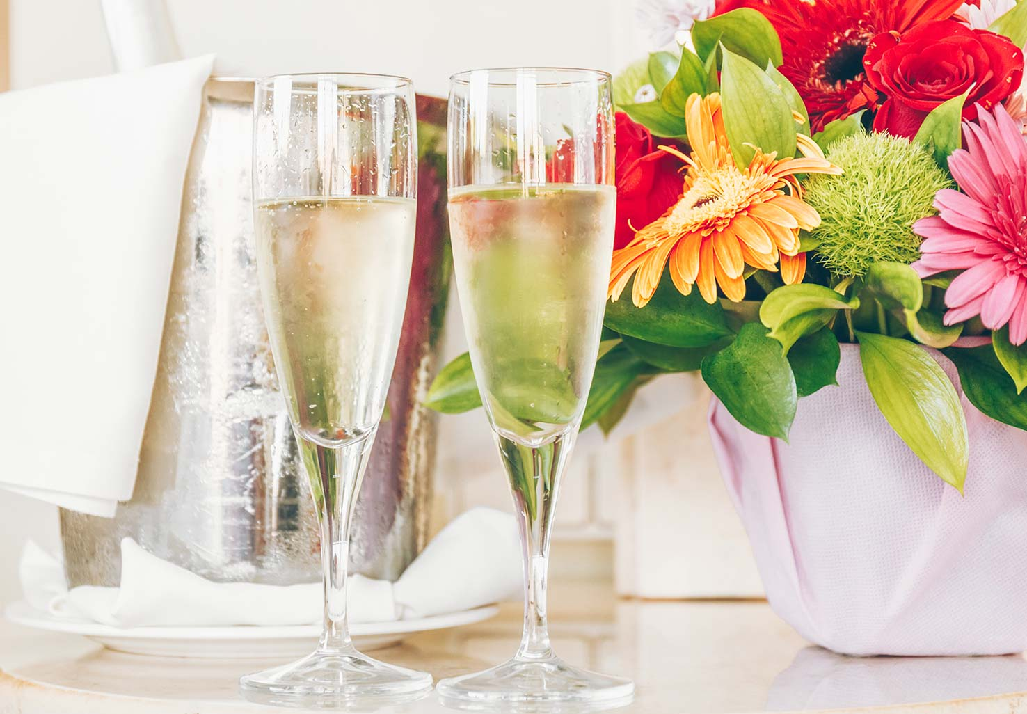 Two flutes of champagne and a small flower arrangement