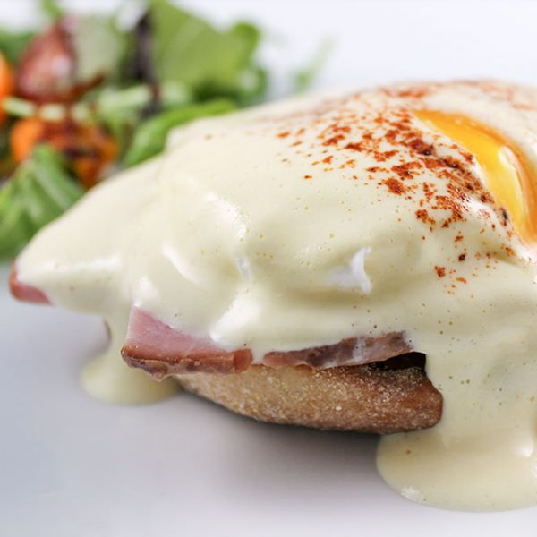 Savory breakfast with eggs Benedict and a side salad