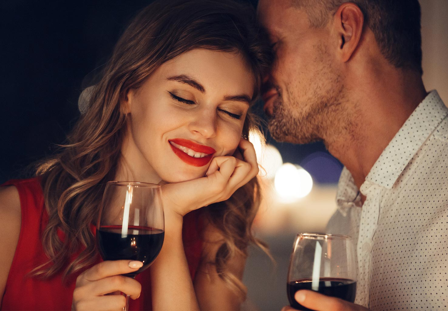 A couple drinking wine sharing a romantic moment