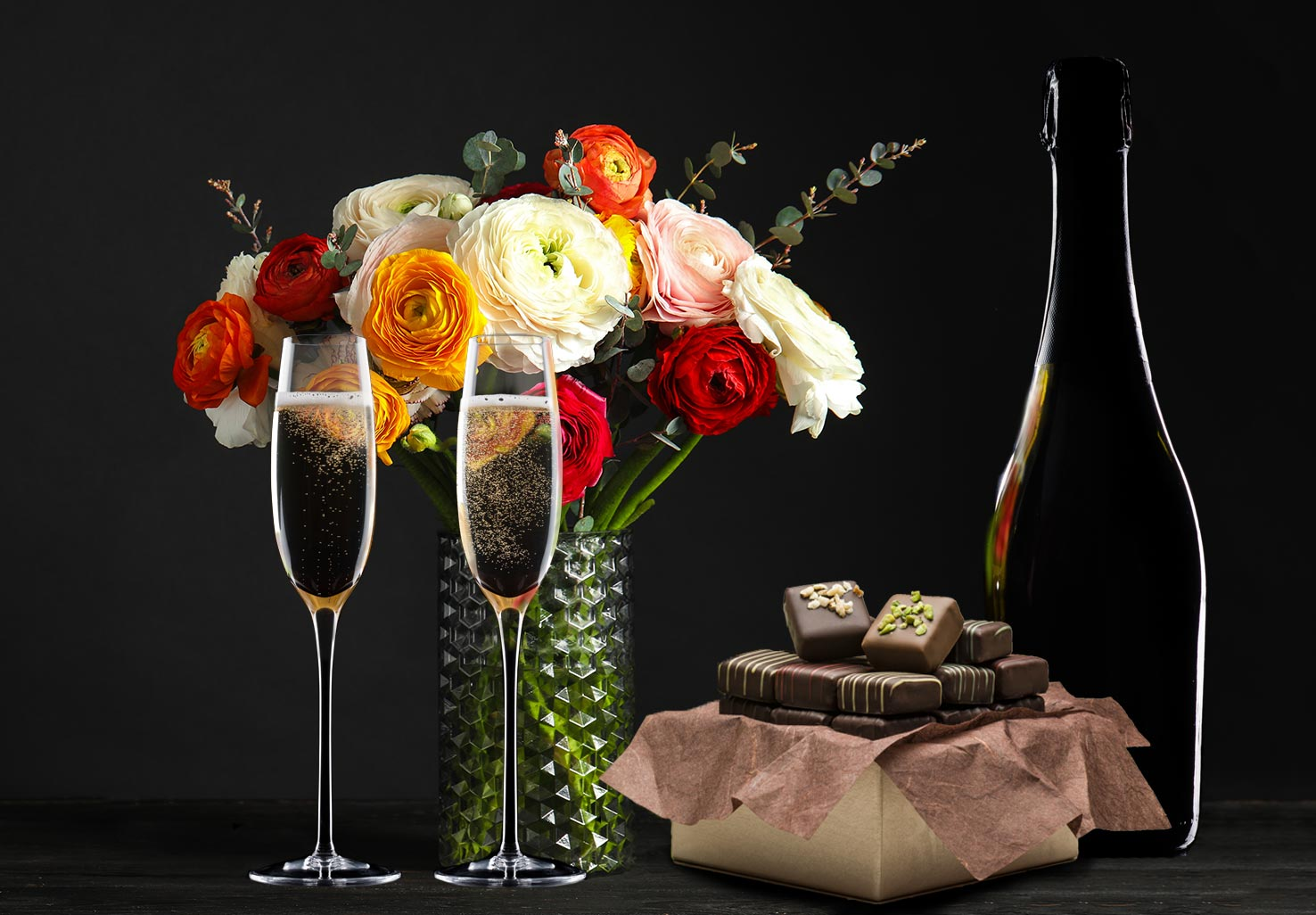 A bouquet of flowers, champagne, and a box of chocolate truffles