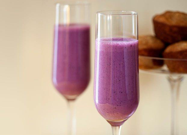 Smoothie in a glass with muffins in the background