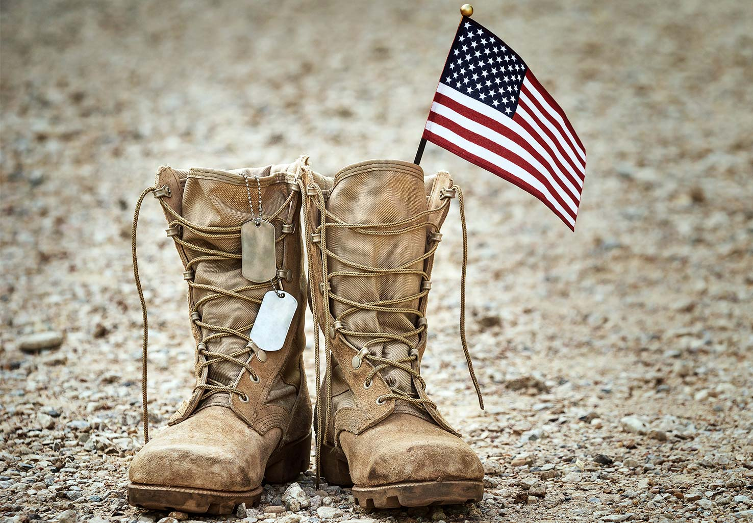 Pair of army boots with a small American flag