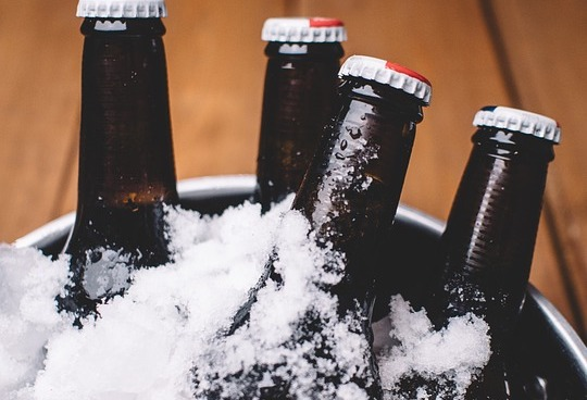Beer bottles in bucket covered with ice