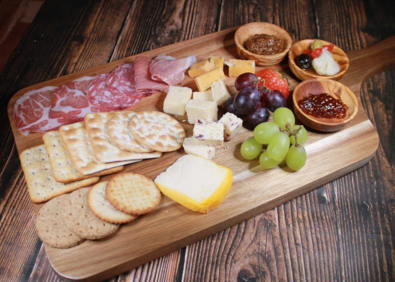 Meat and cheese on a wooden board with grapes