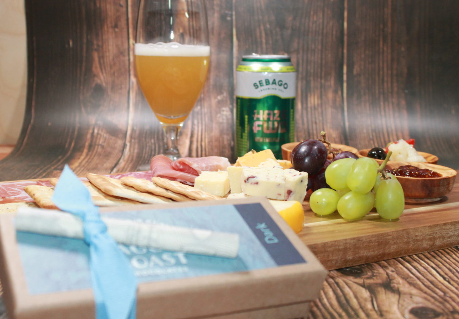 meat and cheese board with can and glass of beer, box of chocolates