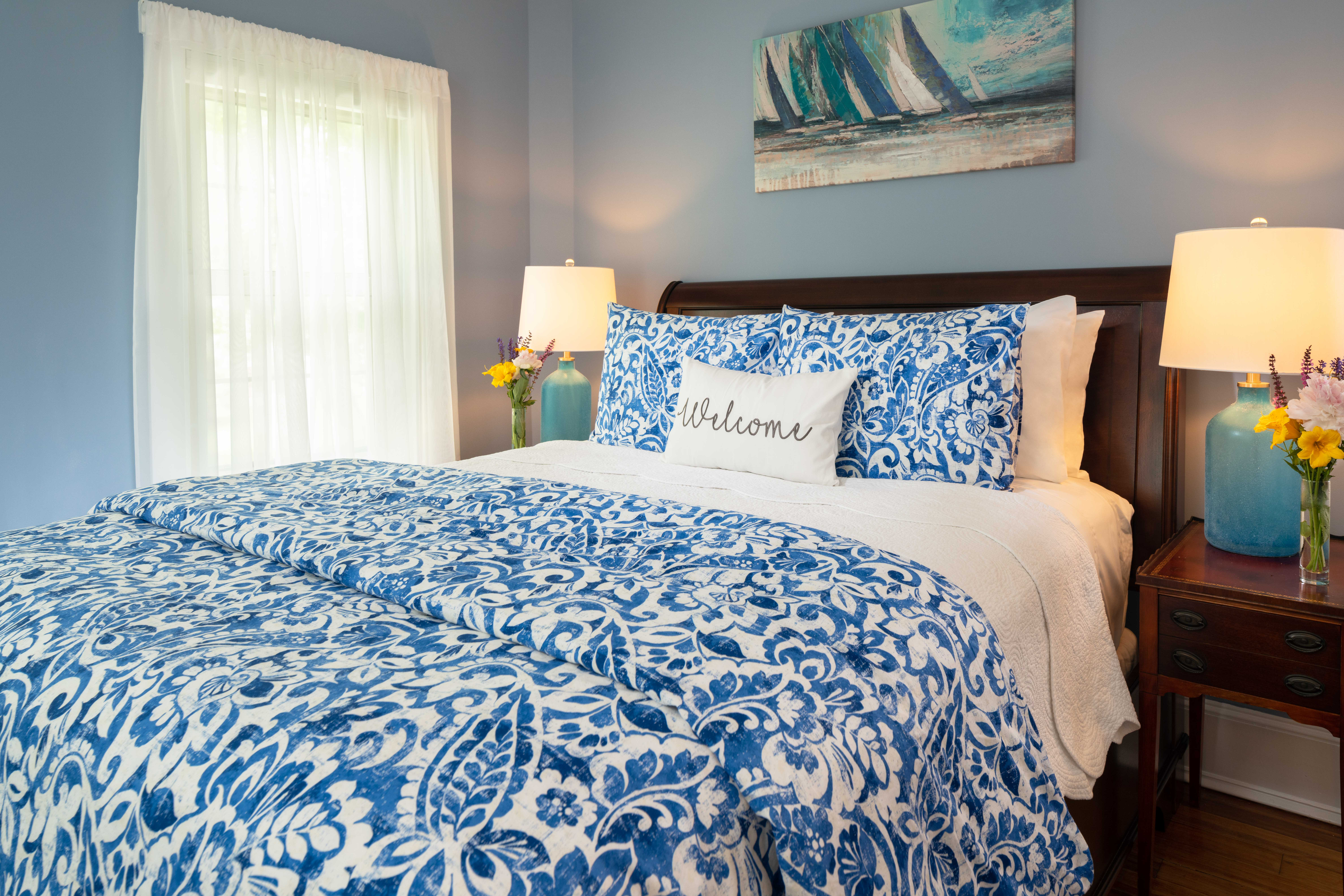Side view of a queen bed in a room with two windows and blue walls