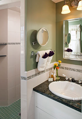 Berwick room bathroom, walk in shower and sink with two hand towels and small pot of flowers