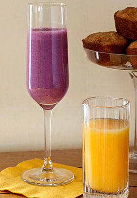 Short glass of orange juice and a champagne glass filled with a blueberry pomegranate smoothie next to a plate of muffins