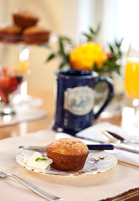 Muffin on a china plate on the dining room table served with a glass of orange juice and a blue mug