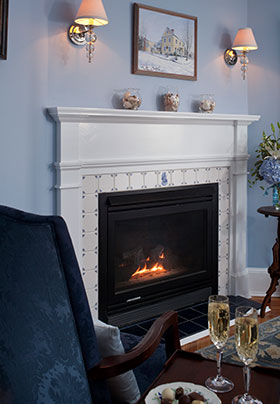 Camden room fireplace with a chair and two champagne glasses fireside