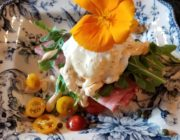 Blue and white plate with sliced tomatoes, poached egg and ham with Arugula and topped with an orange flower.