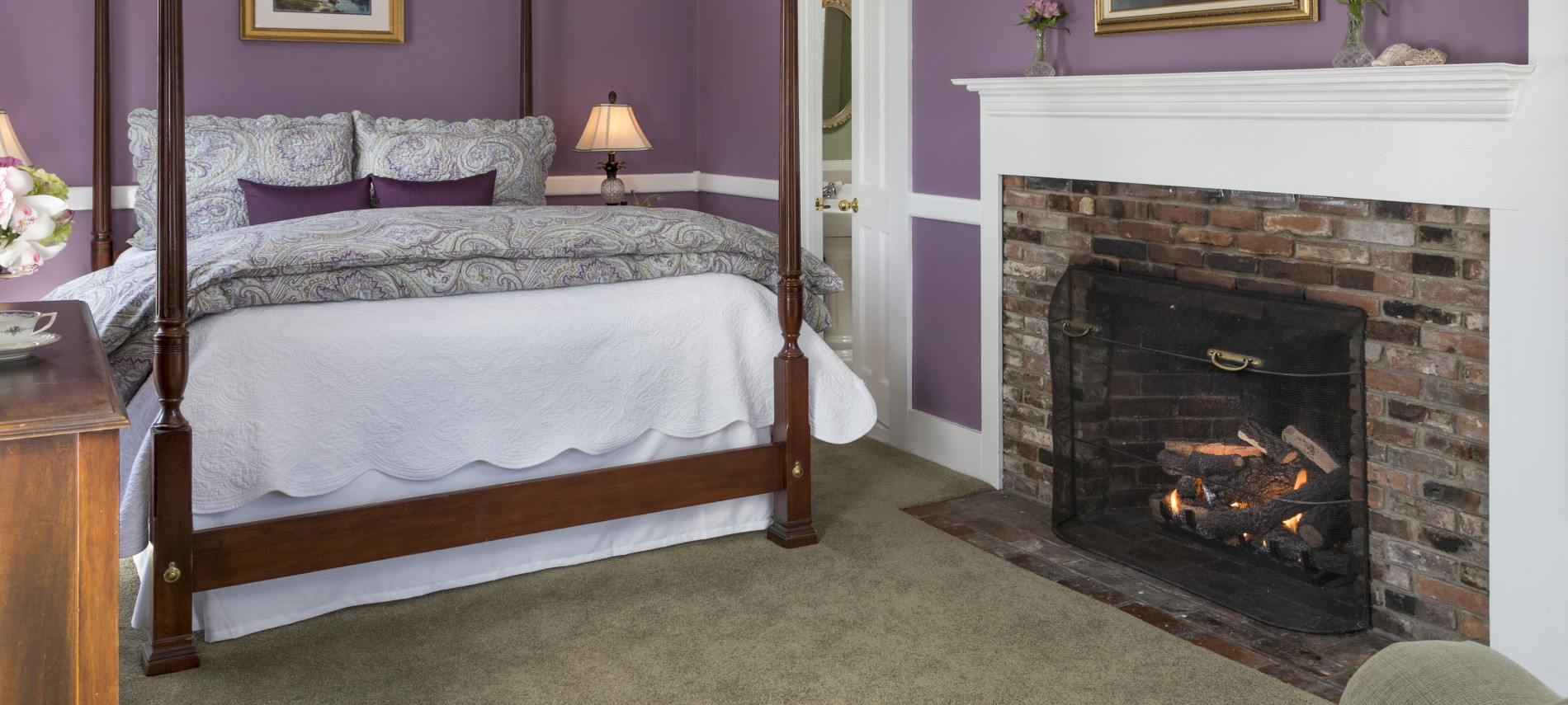 The Windsor room viewed from the couch, featuring a queen sized bed, fireplace, and bedside tables
