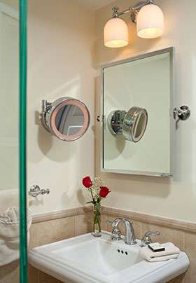 Camden room bathroom sink with round mirror and a small glass of roses on the side of the sink