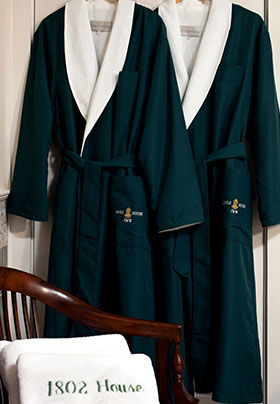 1802 house green robes hung on the door and 1802 House bath mats in from on the couch