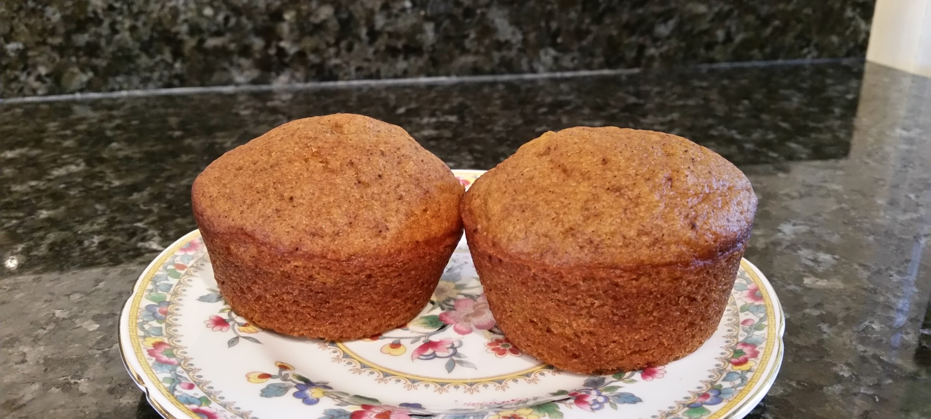 two pumpkin muffins on a china plate