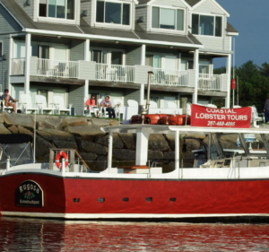 A red boat on the water in front of large grey house and people in white chairs