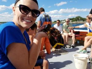 Young girl on lobster boat with other people. Holding a live lobster.