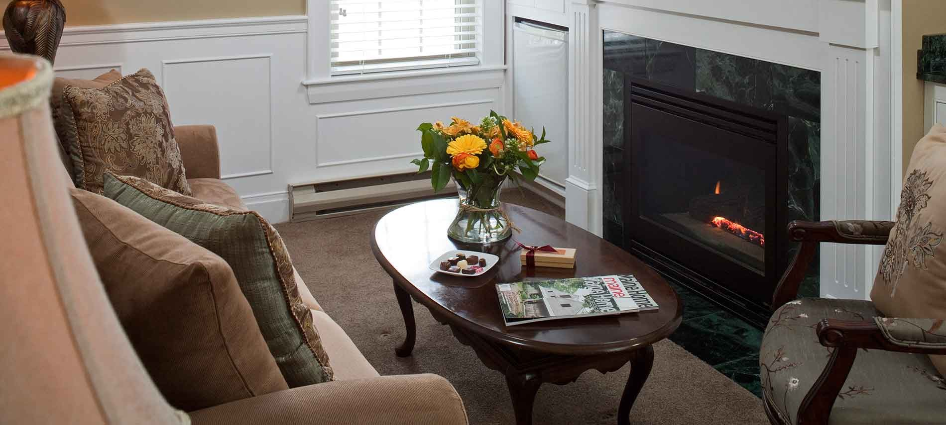 Sebago suite living area with coffee table and bouquet of flowers fireside