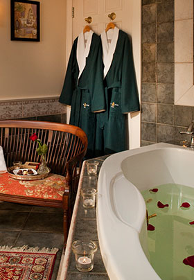 Sebago Suite Jacuzzi room with robes hanging up on the door, rose petals and candles by the jacuzzi and a couch