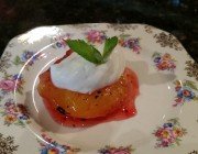 Baked plum topped with greek yogurt, a sprig of mint and a glaze on a china plate