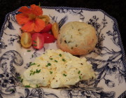 Cheese and chive puff served with scrambled eggs and cherry tomatoes on the side on a china plate